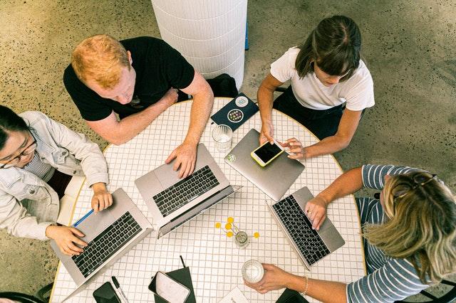 pracownicy w biurze przy stole z laptopami